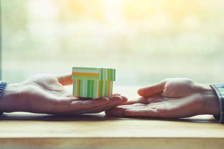 two hands of loving couple with gift box Stock Photo