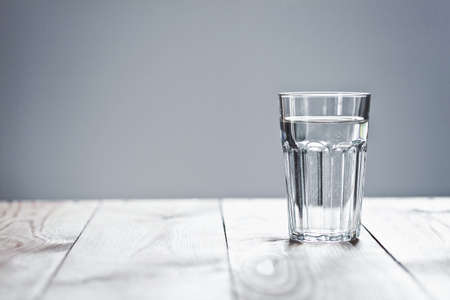 Glass of pure water on neutral background with copy space