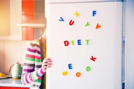 Mujer hambrienta mirando en nevera abierta con letras de dieta en la puerta