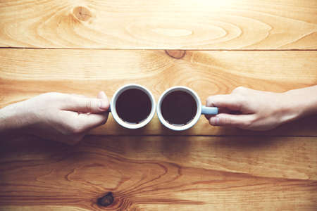 Hands of couple with two cups of morning coffee on wooden table. View from above