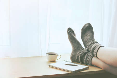 Woman resting keeping legs in warm socks on table with morning coffee and notebook. Space for text Stockfoto