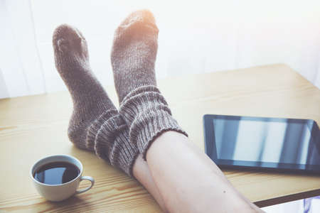 Woman resting keeping legs in warm socks on table with morning coffee and reading e-book or tablet Stock Photo