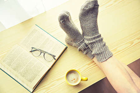 Woman resting keeping legs in warm socks on table with morning coffee and reading book Stock Photo - 105499986
