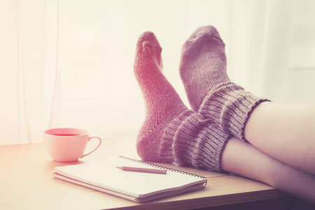 Woman resting keeping legs in warm socks on table with morning coffee and notebook Stock Photo