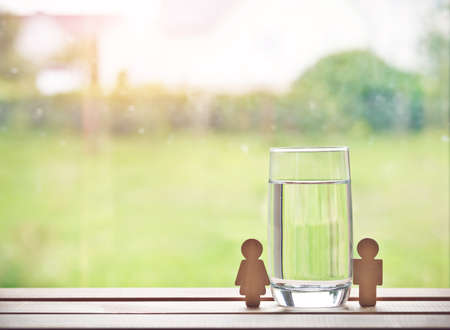 glass of water with wooden woman and man. Space for text Stock Photo - 105499990