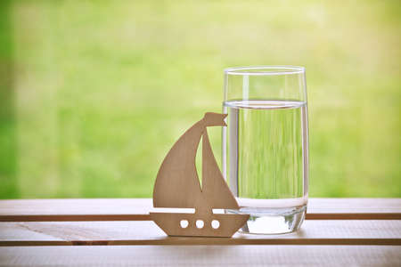 Glass of water with wooden sailing ship. Dreaming concept. Space for text Stock Photo