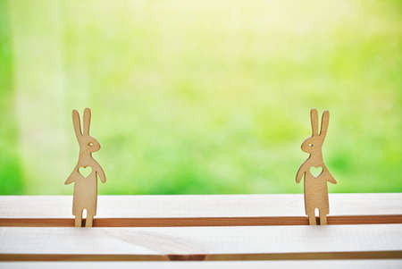 Cute couple of wooden hares in love. Symbol of love and parting