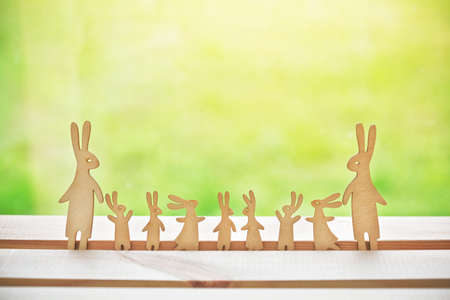 Family of wooden hares with many children. Symbol of happy family and parenthood Stock Photo - 105926775