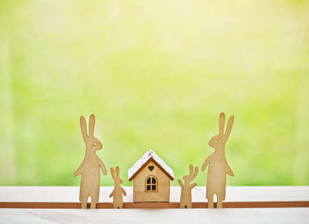 Family of wooden hares near house. Symbol of construction, family, sweet home concept Stock Photo - 105926777