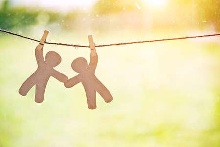 Hölzerne kleine Männer hängen am Seil mit Stift. Symbol für Freundschaft, Hilfe, Unterstützung und Teamwork