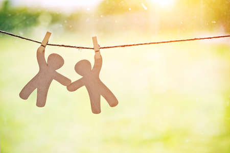 Wooden little men hanging on rope with pin. Symbol of friendship, help, support and teamwork 스톡 콘텐츠