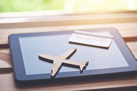 Airplane symbol with credit card and tablet computer. Online ticket booking concept Stock Photo
