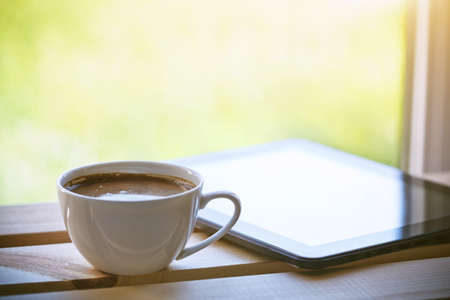 Cup of morning coffee with tablet computer