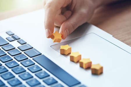 La mano da una calificación de cinco estrellas como retroalimentación del producto con la computadora portátil.