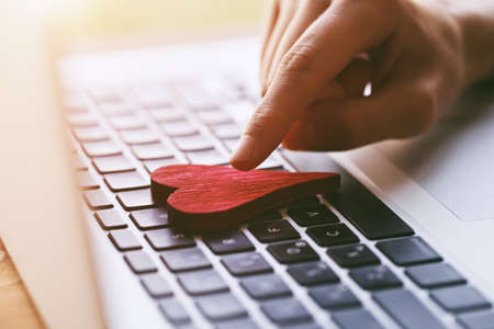 hand giving heart with laptop as like symbol in social media for posts and photos