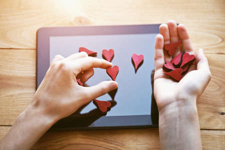 hand collecting hearts as like symbol in social media for posts and photos