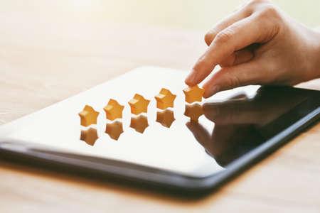 Hand gibt fünf Sterne Bewertung als Produktfeedback mit Tablet-Computer