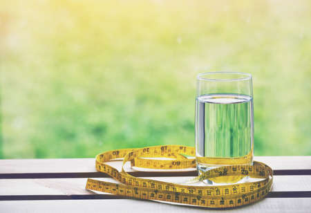 Glass of pure natural water and yellow measuring tape on natural background. Symbol of health and diet Stock Photo