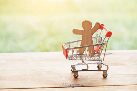 toy trolley with little wooden man as symbol of shopping and happy customer
