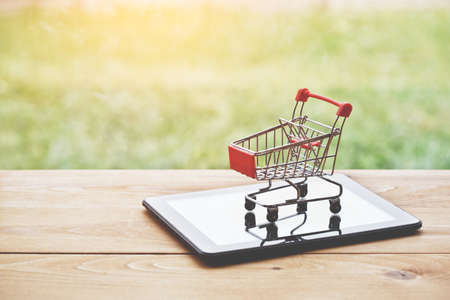 digital tablet  with trolley as symbol of online shopping and paying Stock Photo