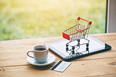 coffee cup and digital tablet with credit card and trolley as symbol of online shopping and paying Stock Photo