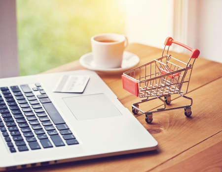 laptop with credit card and trolley as symbol of online shopping and paying Stock Photo