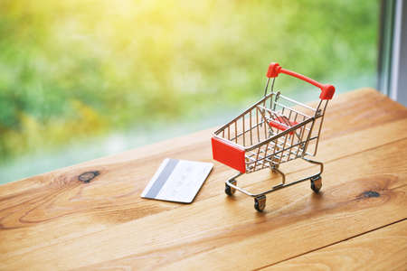 toy trolley with credit card as symbol of shopping and paying Stock Photo