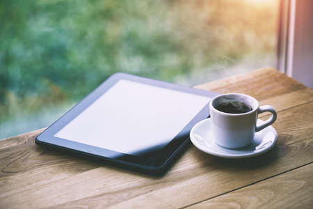 morning coffee cup and digital tablet on wooden table near window