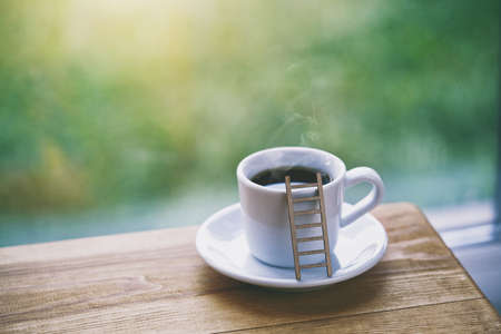 cup of fresh morning coffee with toy ladder as symbol of sinking in aroma and taste Stock Photo