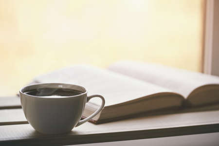 hot coffee and book in morning sunlight Stock Photo