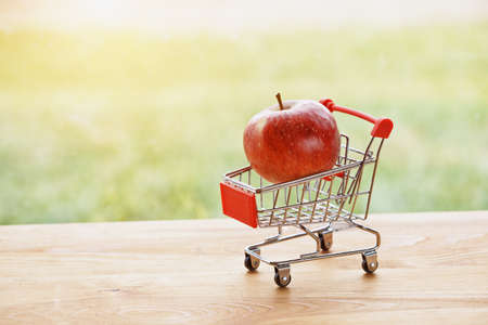 toy trolley with apple as symbol of shopping and paying Stock Photo