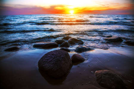 Peaceful sunrise at sea with stones