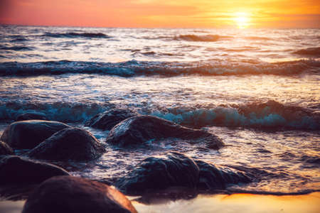 Beautiful sunset at sea with waves Stock Photo