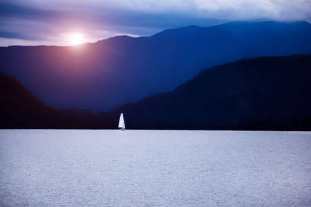Magical scenery with sailboat on lake in sunrise light