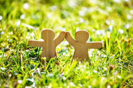 Wooden little men holding hands. Teamwork, friendship and love concept