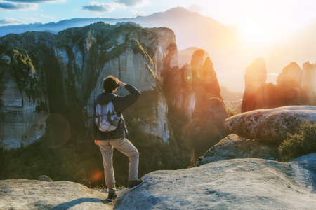 woman with backpack enjoying sunrise on top of mountain  Stock Photo