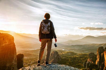 woman with camera enjoying sunset on top of mountain