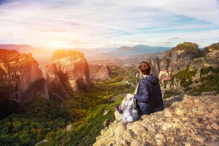 woman enjoying sunrise sitting on top of mountain  Stock Photo