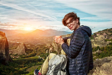 woman with cup of coffee resting and enjoying scenery on mountain