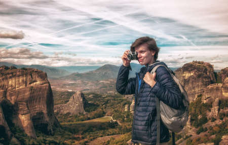 woman with photo camera enjoying scenery on top of mountain
