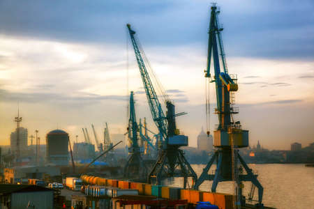 Industrial cranes loading freight containers for cargo ships. Logistic and transportation concept. Stock Photo