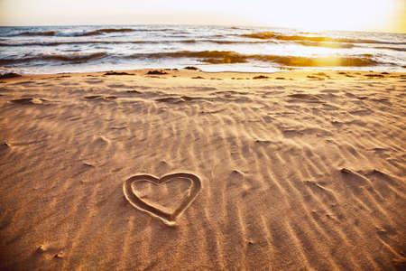 Drawn heart shape on sea sand beach. Love concept