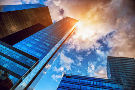 View of geometric business center skyscrapers with sunny sky reflection