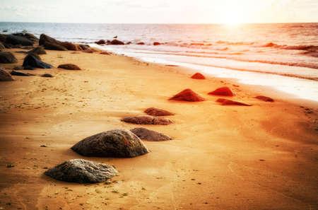 Peaceful sunrise at seaside beach with stones