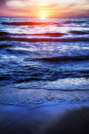 Peaceful sunset at sea with waves