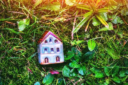 Model of ceramic house in grass as symbol
