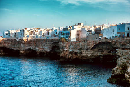View of rocky seashore with town buildings. Polignano a Mare, Italy. Stock Photo
