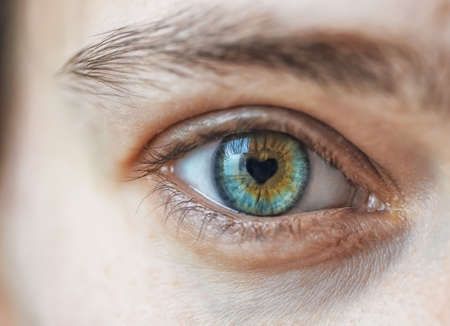 Close up of woman eye with heart shape pupil. Love and passion concept Stock Photo