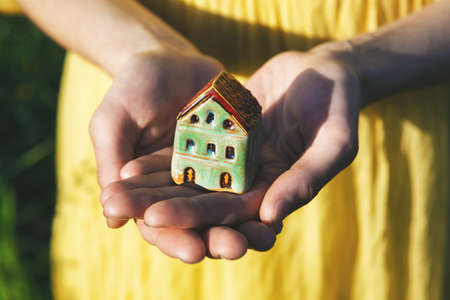 Hands holding model of house as symbol Imagens