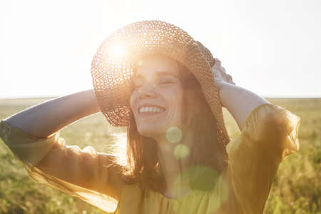 Portrait of happy pretty woman with hat smiling and enjoying summer sunlght in meadow   Imagens